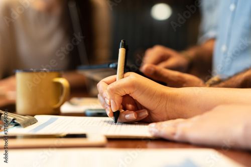 close up detail of latin hands with pen writing notes on clipboard in co-working open space. Communication, workspace, meeting concept..
