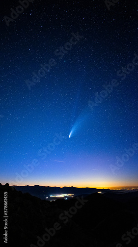 Vertical shot of a shooting star in the gorgeous sky over a city at dusk