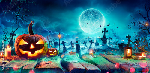 Fototapeta Jack O' Lantern On Table In Spooky Graveyard At Night - Halloween With Full Moon obraz