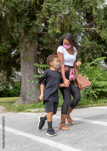 Black African American Mother and Son Crossing Street Wearing PPE Face Masks to Fototapeta