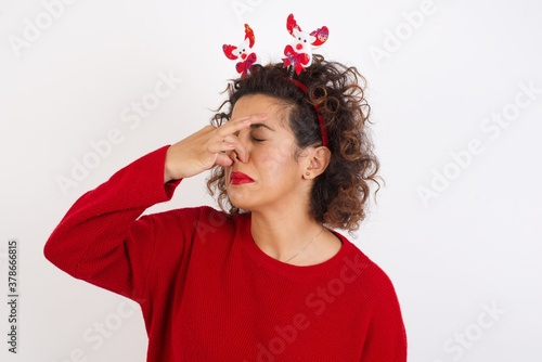 Young arab woman with curly hair wearing christmas headband standing on white background smelling something stinky and disgusting, intolerable smell, holding breath with fingers on nose Fototapeta