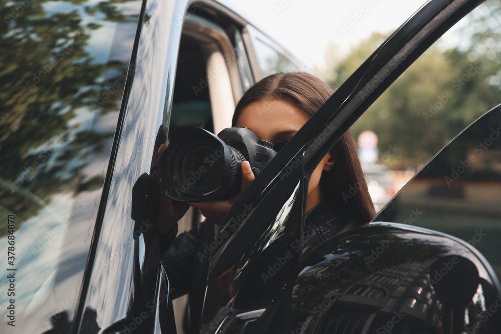 Fototapeta Private detective with camera spying near car outdoors