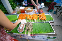 An Asian Traveler Is Selecting And Buying River Shrimp Grilled Put On The Banana Leaf In The Walking Street At  Local Food Night Market North Of Thailand