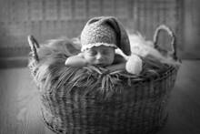 A Small Child In A Basket Slee...