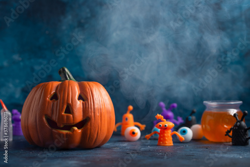 Halloween banner with angry smiling pumpkin isolated on dark blue background. The artificial eyes and strange little men are for scenery. Halloween concept.