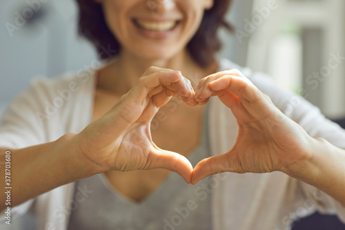 Fototapeta Cropped shallow focus image of happy smiling lady showing heart symbol with her hands obraz
