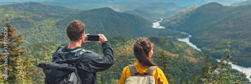 Fototapeta Hikers couple camping walking with backpacks in Quebec taking picture of view with phone in Autumn. Canada forest travel lifestyle banner. Tourists looking at Jacques Cartier National Park. obraz