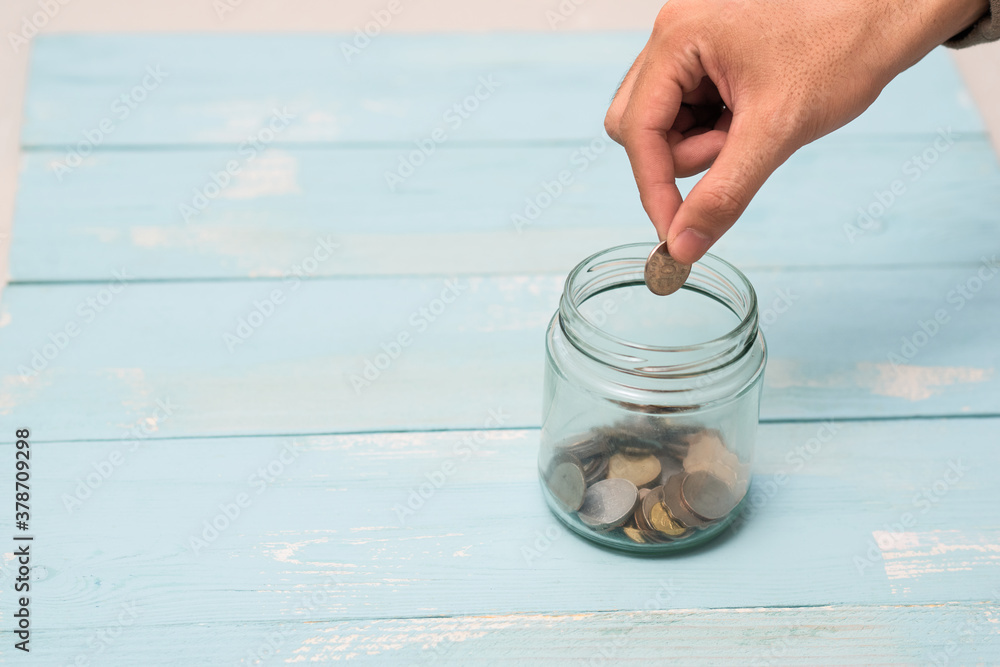 Fototapeta Hand putting Coins in glass jar with blank empty label for giving and donation money concept