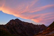 北アルプスの最難関の岩陵帯、劔岳の稜線、岩肌、夕映えの空。スカイライン。シルエット。秋晴れ。雲。旅行、旅先、シルバーウィーク、紅葉、黄葉。
