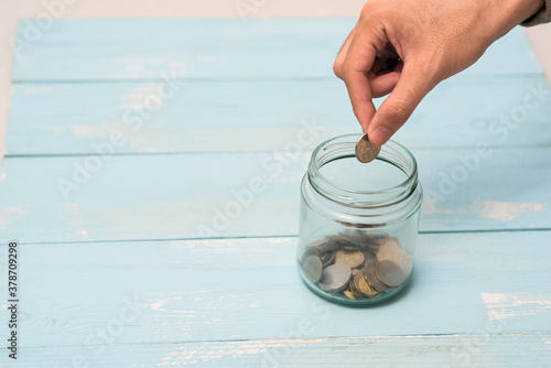 Hand putting Coins in glass jar with blank empty label for giving and donation m Fototapet