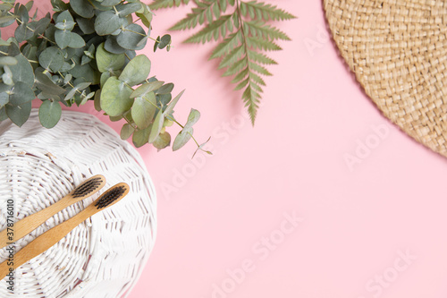 Obraz Bamboo toothbrush and leaves of eucalyptus on pink background. - fototapety do salonu