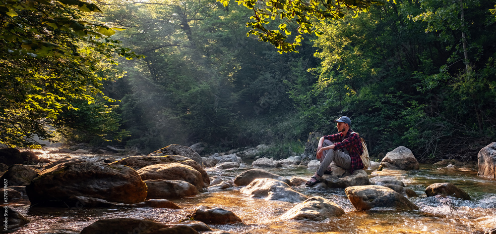 Fototapeta Happy male hiker trekking outdoors in forest near river