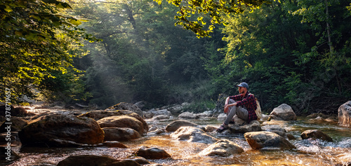 Obraz Happy male hiker trekking outdoors in forest near river - fototapety do salonu