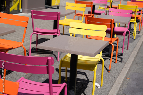 Fototapeta Charming yellow orange and pink chairs on cafe outdoor restaurant cafe and wooden tables colorful terrace obraz