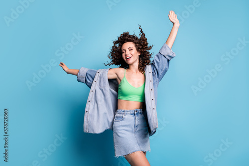 Fototapeta Photo of cute charming young lady smiling closed eyes hands raised up carefree dance village discotheque wear denim mini skirt shirt green crop top isolated blue color background obraz
