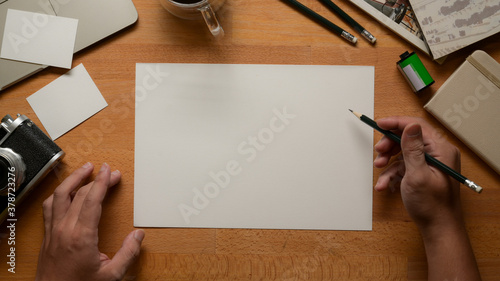 Male artist working with blank sketch paper, pencils, camera and supplies on wor Canvas Print