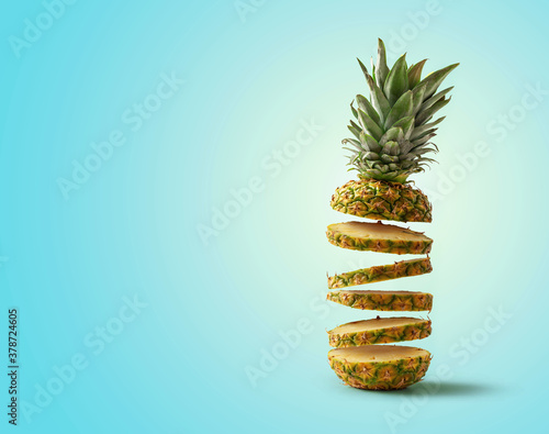 Tela Fresh pineapple cut into slices flying, isolated from the blue background with c