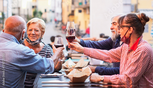 Group of old people eating and drinking outdoor - Doubble date with facemask on Fotobehang