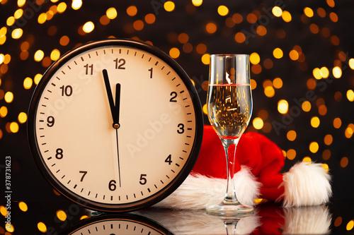 Obraz na plátně New Year eve concept with alarm clock against blurred garland