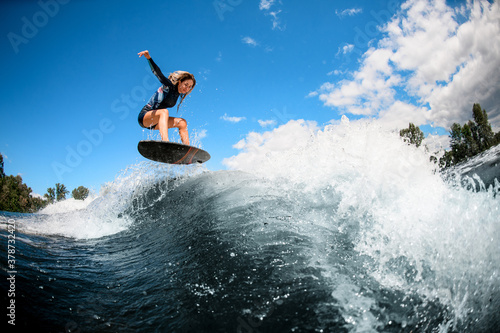 Obrazy Sporty Wodne   beautiful-view-of-young-woman-on-surfboard-jumping-over-the-wave