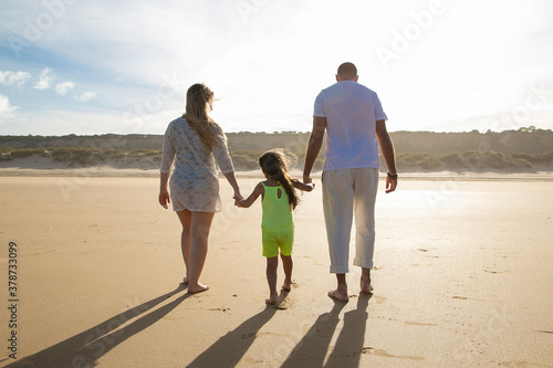 Foto Young parents and kid in summer clothes walking on golden sand against sun, mom and dad holding girls hands