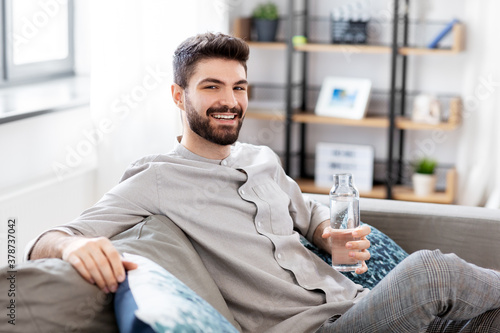 people, sustainability and leisure concept - happy smiling young man sitting on sofa and drinking water from glass bottle at home