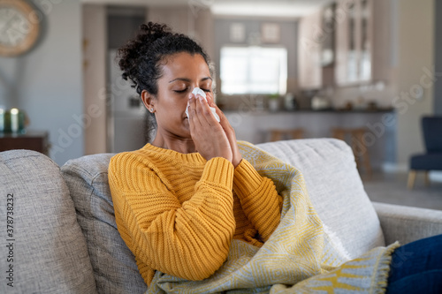 Cold sick african woman blowing nose