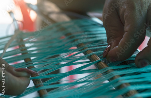 Fototapeta Woman working on weaving machine for weave handmade fabric. Textile weaving. Weaving using traditional hand weaving loom on cotton strands. Textile or cloth production in Thailand. Asian culture. obraz