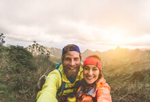 Happy Couple Taking Selfie While Doing Trekking Excursion On Mountains - Young Hikers Having Fun On Exploration Nature Tour - Relationship And Travel Vacation Lifestyle Concept