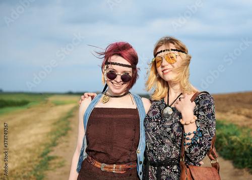 Fotomural Two hippie women, wearing boho style clothes, walking on dirt road on green field, having fun