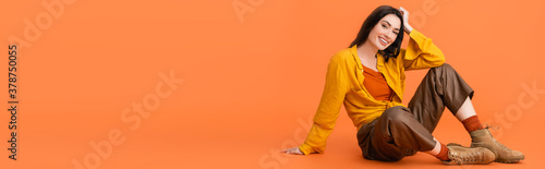 panoramic concept of brunette and trendy woman in autumn outfit sitting on orange