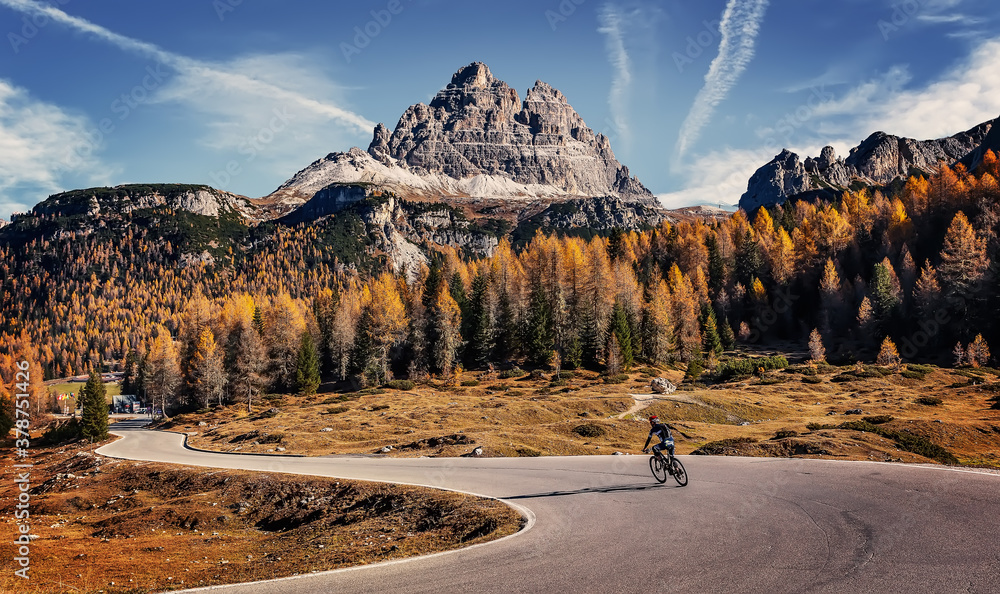 Fototapeta Amazing mountain landscape at autumn sunny day. scenic alpine scenery of Dolomites Alps. Wonderful view on Mountain valley, forest, and asphalt road for majestic rocky peak. travel on bike concept.