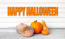 Text Of Happy Halloween Near Orange Pumpkins On The Background Of White Wall With Lines.