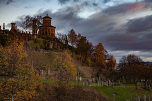 Glasgow / Scotland - Nov 13, 2013: Glasgow Necropolis Hill In Fall. Grave Monuments And Mausoleum. Green Grass And Yellow Trees. Yellow Light Of Sunset. Grey Cloudy Sky. Panorama View.