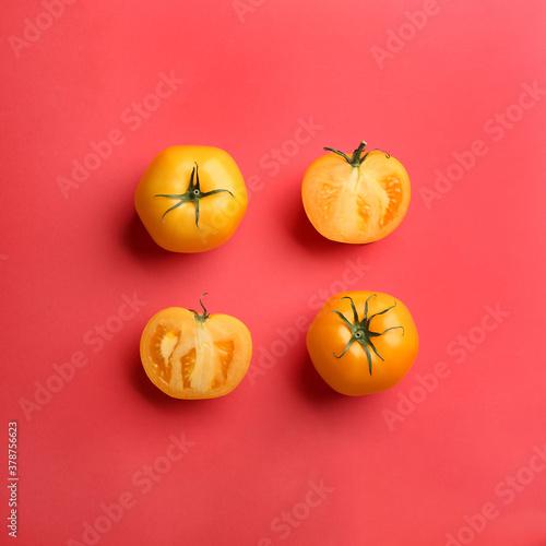 Fototapeta Yellow tomatoes on red background, flat lay obraz