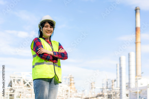 Fototapeta Asian woman engineer arm crossed and smile with confident looking forward to future with oil refinery plant factory in background. obraz