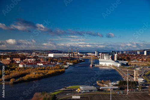 Glasgow / Scotland - Nov 13, 2013: Fall in the city. Clyde river embankment. Riverside Museum and The Tall Ship at Riverside. Panorama view. Yellow trees. Blue sky with clouds.