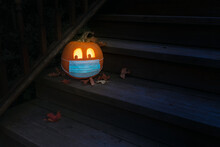Lighted Carved Jack-o-Lantern Dressed Up For Halloween With COVID Pandemic Face Mask - Wide Angle Horizontal