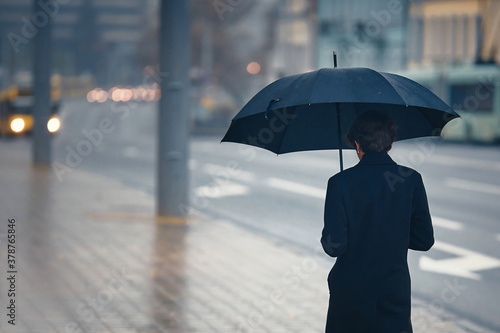 Stylish man with umbrella in rainy foggy day walking alone down the city street Wallpaper Mural