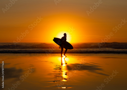 Obraz na plátně Silhouetted Surfer at Sunset on Widemouth Bay - Bude, Cornwall, England