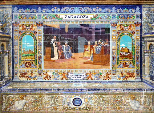 Image with the name of the spanish city of Zaragoza and a historical scene painted on ceramic tiles - seating benches in Spain Square in Seville