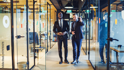 Fototapeta Successful businessmen in formal wear discussing trade project while walking in financial company, diverse entrepreneurs in stylish suits have office excursion for looking around tenement workspace obraz