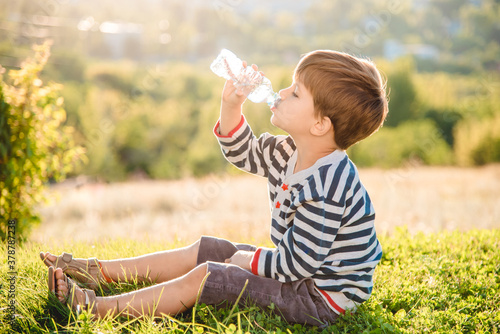 Photo Cute boy sitting on the grass drinks water from a bottle in the summer at sunset