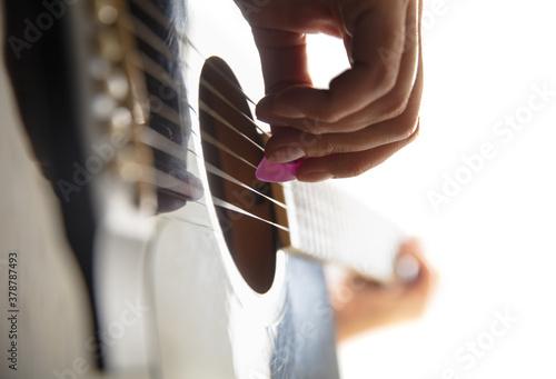 Fényképezés Close up of guitarist hand playing guitar, macro shot