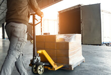 Cargo Shipment, Delivery, Freight Truck Transportation And Logistics. Warehouse Worker Working With Hand Pallet Truck Loading Carton Boxes On Pallet Into Cargo Container.