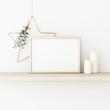Horizontal frame mockup with gold matal star, eucalyptus, pine cones and candles on empty white wall background. Minimalist Christmas interior decoration. A4, A3 format. 3d rendering, illustration