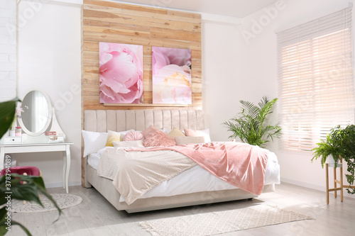 Fototapeta Stylish room interior with large comfortable bed and beautiful paintings obraz