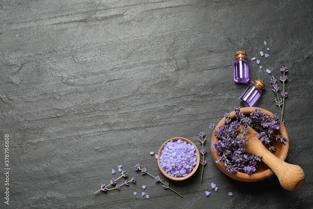 Fototapeta Cosmetic products and lavender flowers on dark grey background, flat lay. Space for text