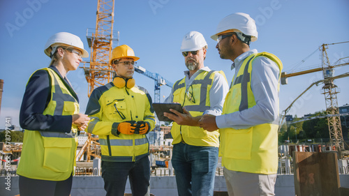 Fototapeta Diverse Team of Specialists Use Tablet Computer on Construction Site. Real Estate Building Project with Civil Engineer, Architect, Business Investor and General Worker Discussing Plan Details. obraz