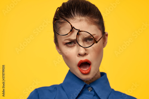 Fototapeta emotional woman with glasses on her face grimacing on yellow background